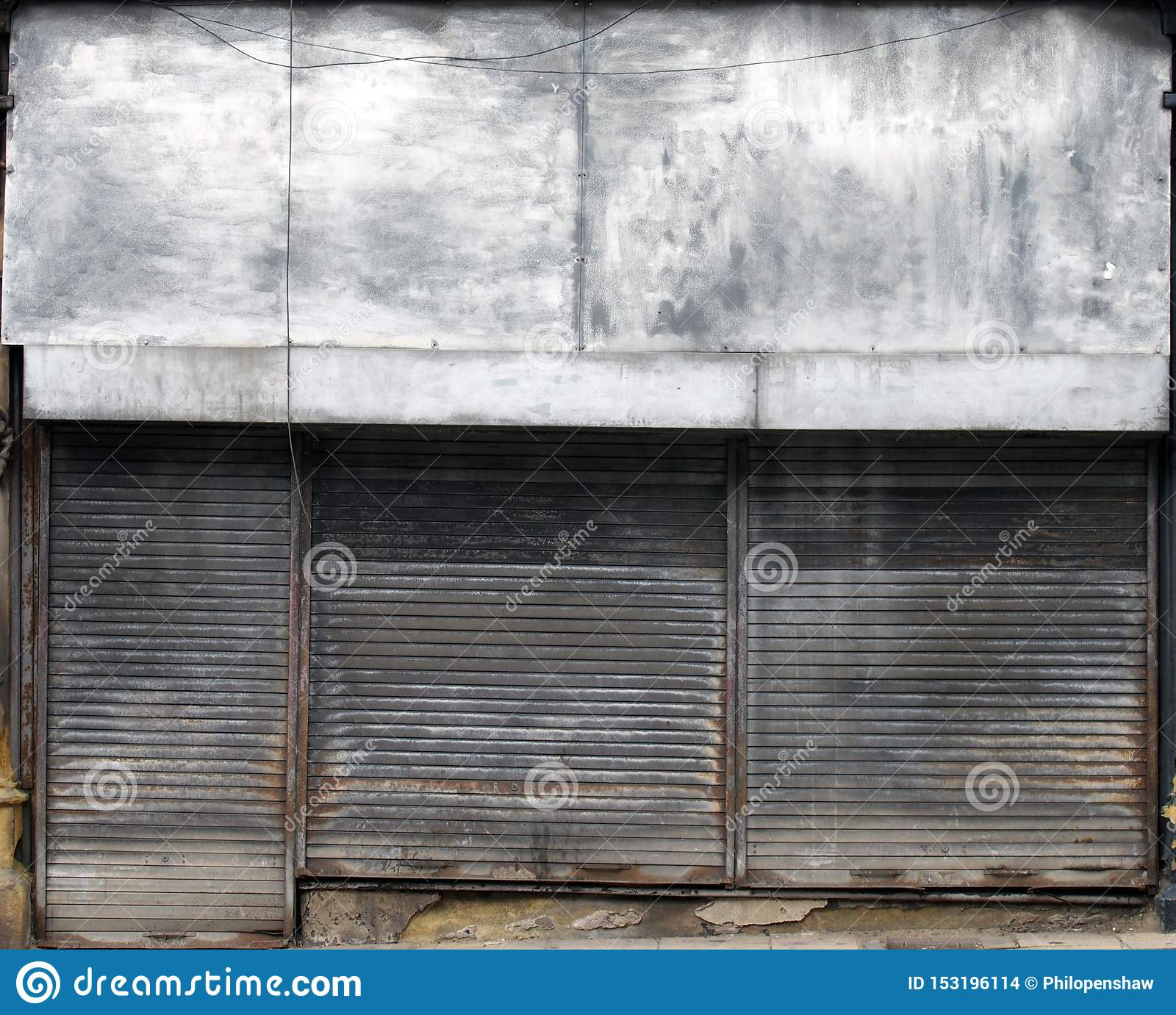 The front of an abandoned store on a street with closed rusting metal shutters over the shop front and door