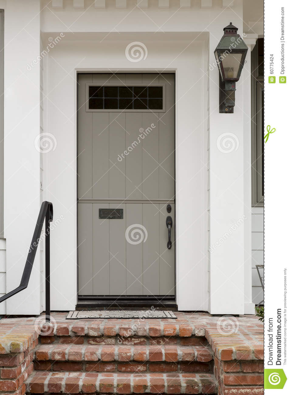 front door with white exterior and a large porch light with brick staircase stock photo