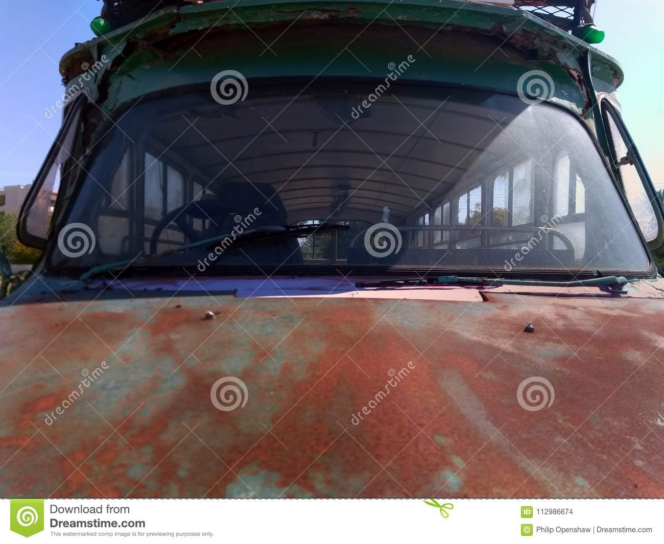 Front end detail of an old abandoned rusty bus with hood and windscreen
