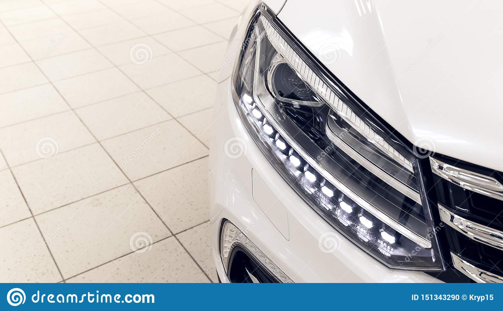 The front lights of the modern white car with LEDs. The car is in the showroom on a sunny day