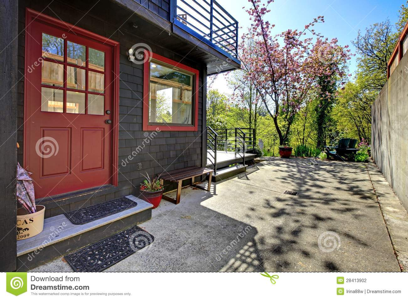 Front Red Door Of Black Wood House With Garden View Stock
