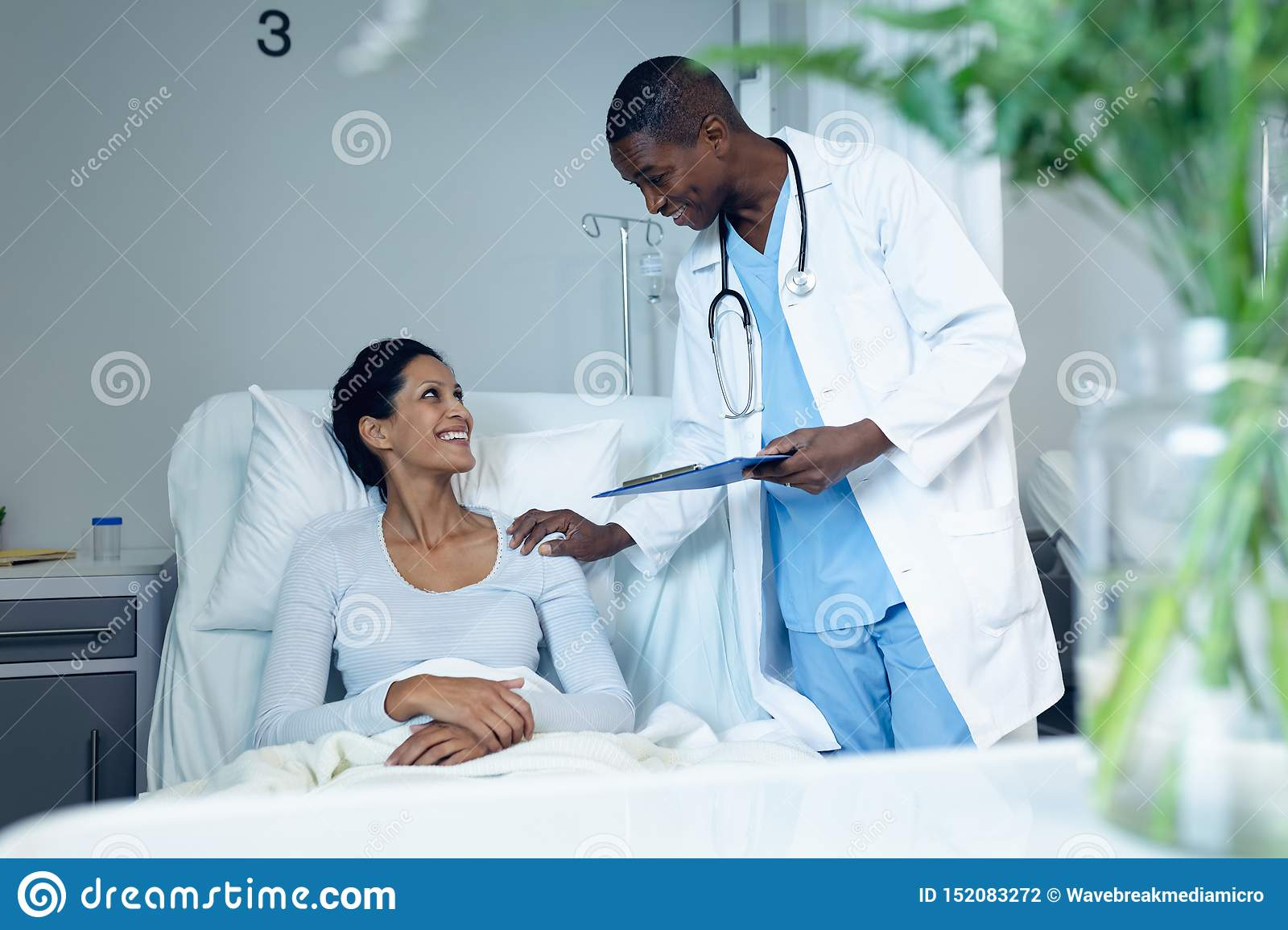 Male doctor interacting with female patient in the ward