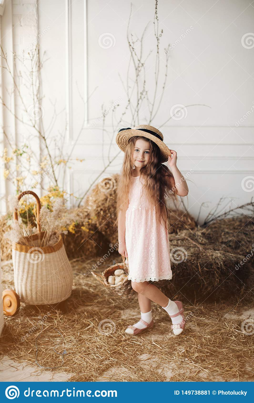 Girl in dress and hay hat keeping basket with little chick