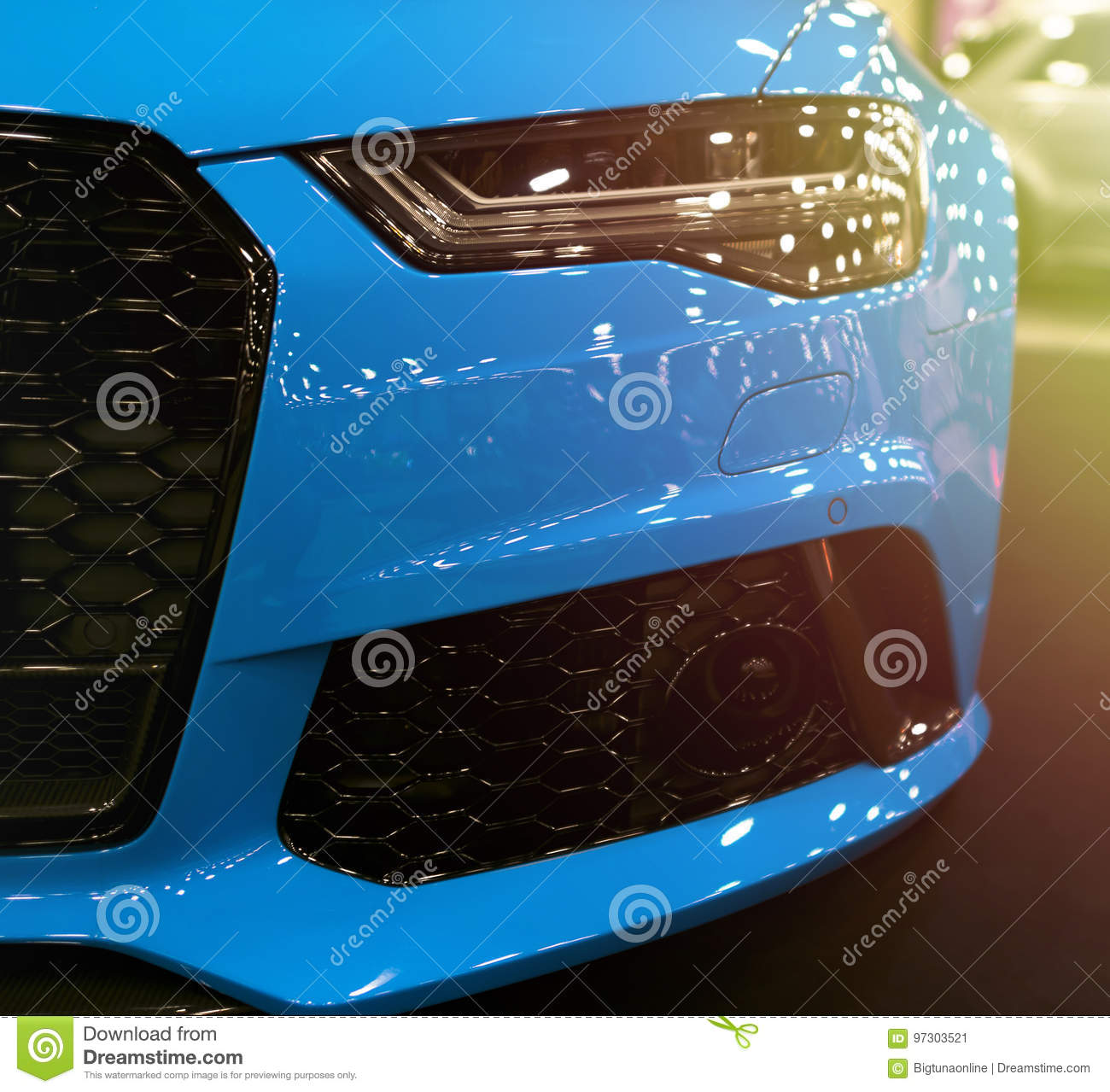 Front view of blue modern luxury sport with soft orange sun light. Car exterior details. Headlight of a modern sport car.