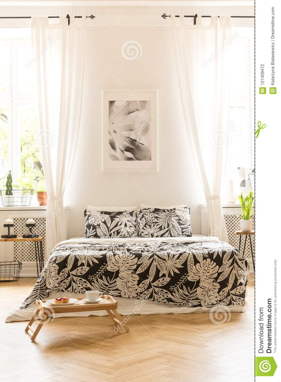 Front View Of A Double Bed With Floral Sheets, Graphic On The Wa