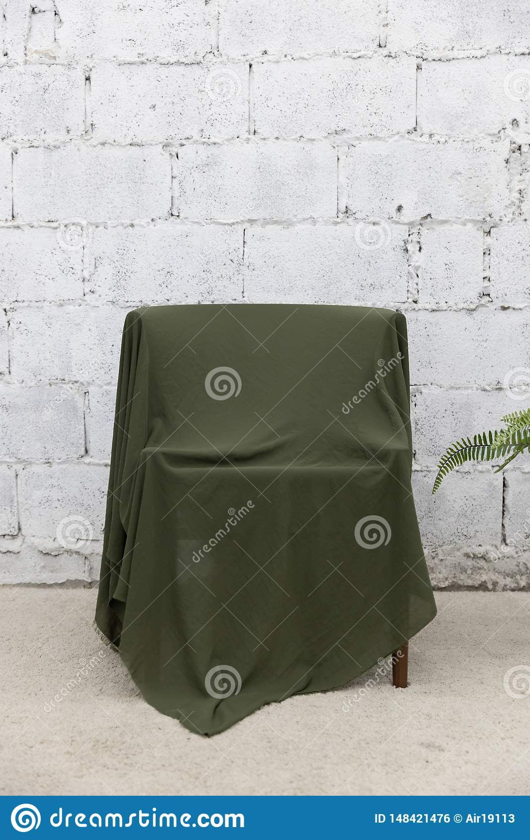 Front view of green cloth cover the wooden chair with gray cement wall and carpet