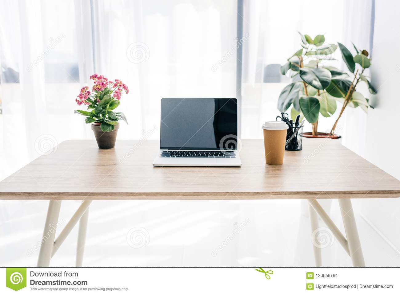 front view of laptop with blank screen, coffee cup, flowers and stationery