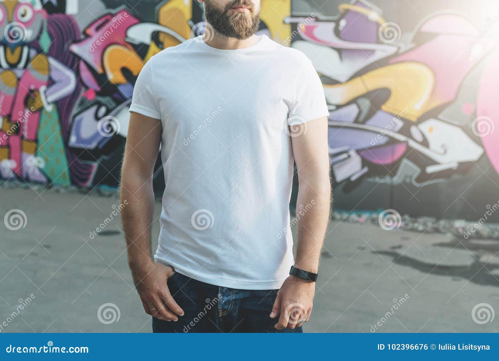 Front View Le jeune homme barbu de hippie habillé dans le T-shirt blanc est des positions contre le mur avec le graffiti Voir les