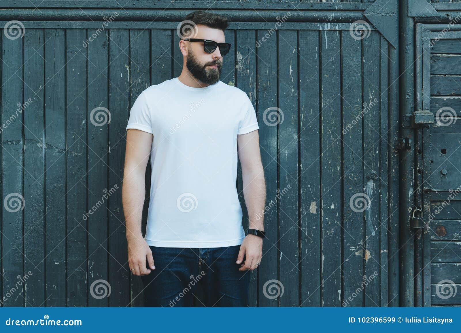 Front View Le jeune homme barbu de hippie habillé dans le T-shirt et des lunettes de soleil blancs est des positions contre le mu