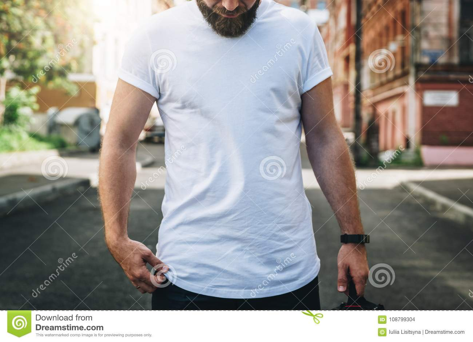 Front View Le jeune homme millénaire barbu habillé dans le T-shirt blanc est des supports sur la rue de ville Voir les mes autres