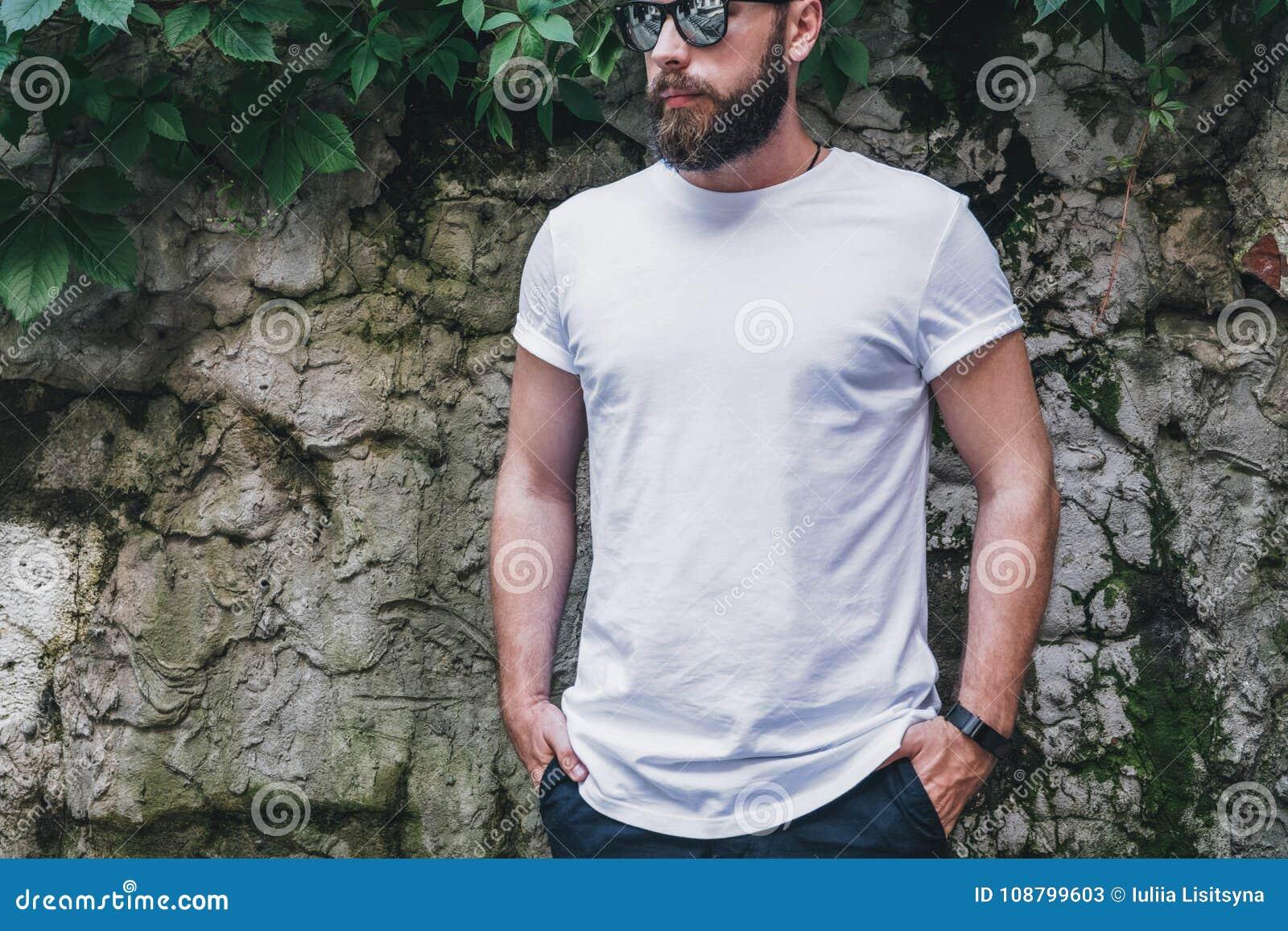Front View Le jeune homme millénaire barbu habillé dans le T-shirt et des lunettes de soleil blancs est des positions contre le m