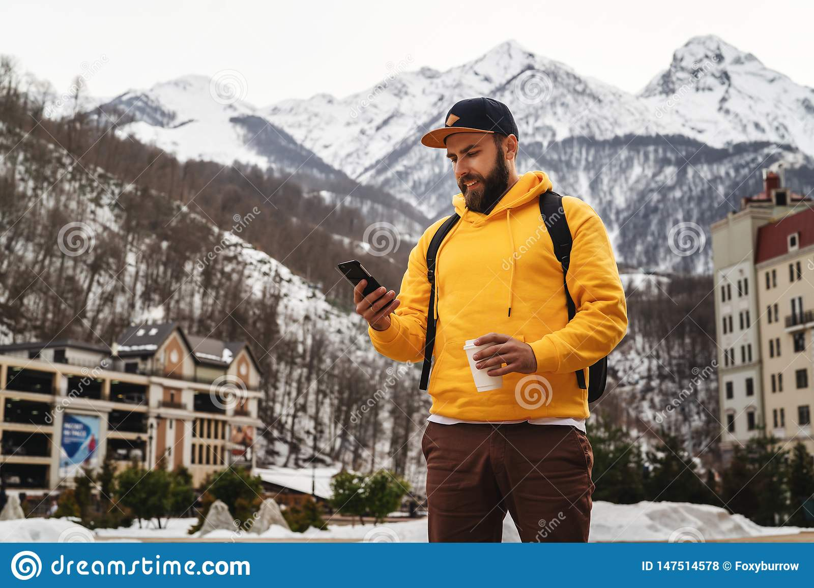 Front view. Man tourist in yellow hoodie, cap with backpack stands on background of high snowy mountains and using smartphone