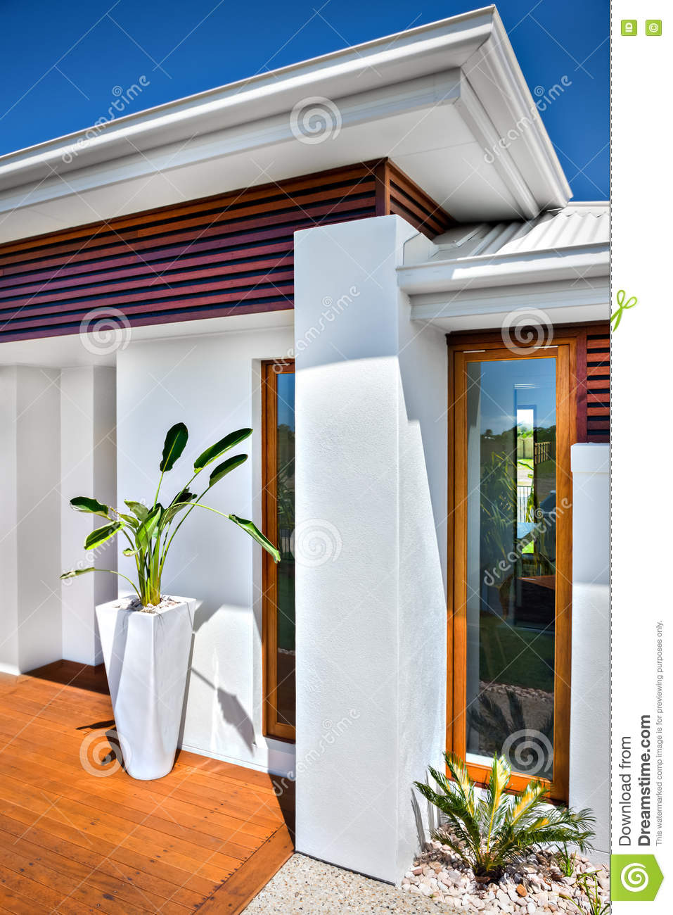 Close up of a luxury house entrance with a facade that has a wooden floor there are two glass windows near to the entrance and green plant in a white vase