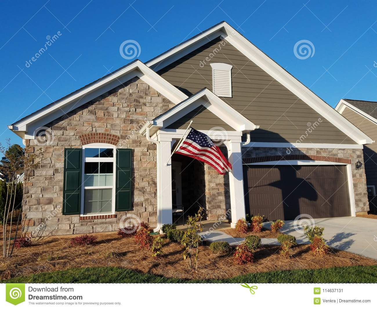 A front view of the modern house with stones and us flag
