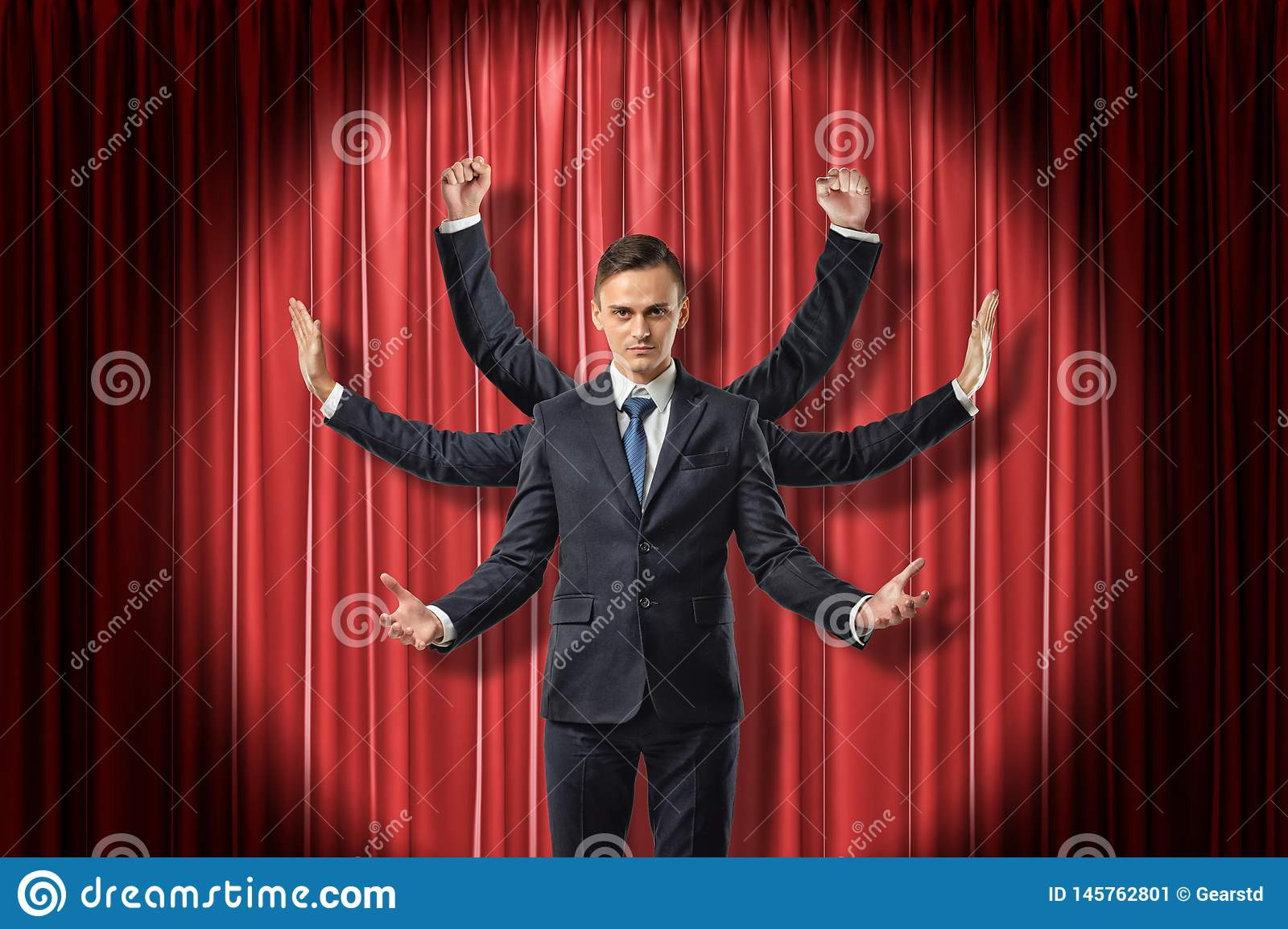 Front view of multiarmed businessman raising hands like Shiva, standing lit up by spotlight against red stage curtain.