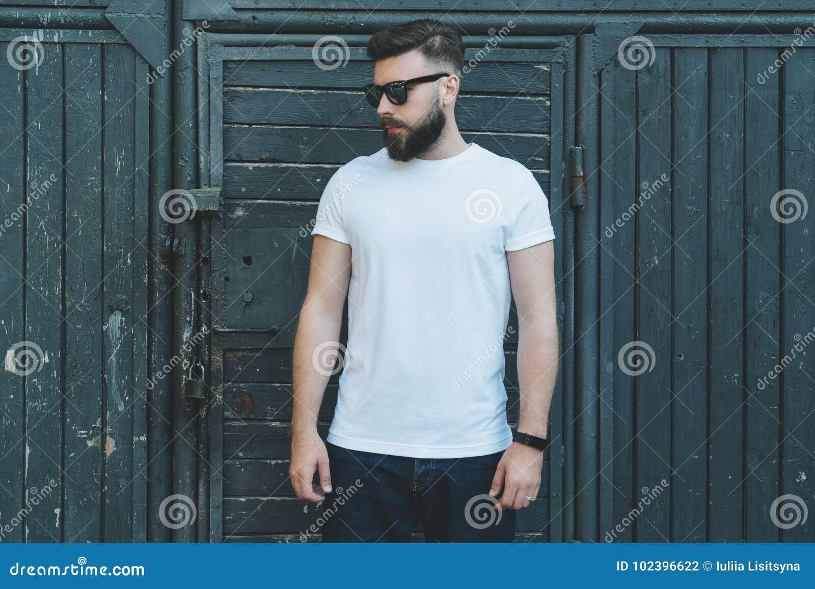 Front View O homem farpado novo do moderno vestido no t-shirt e nos óculos de sol brancos é suportes contra a parede de madeira e