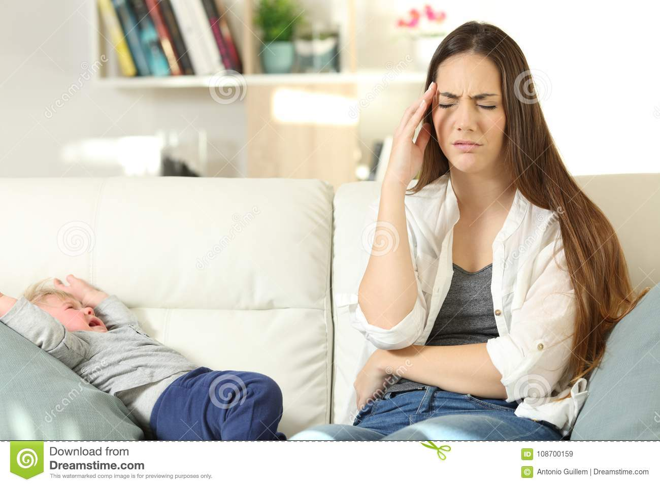 Annoyed mother and baby crying on a couch