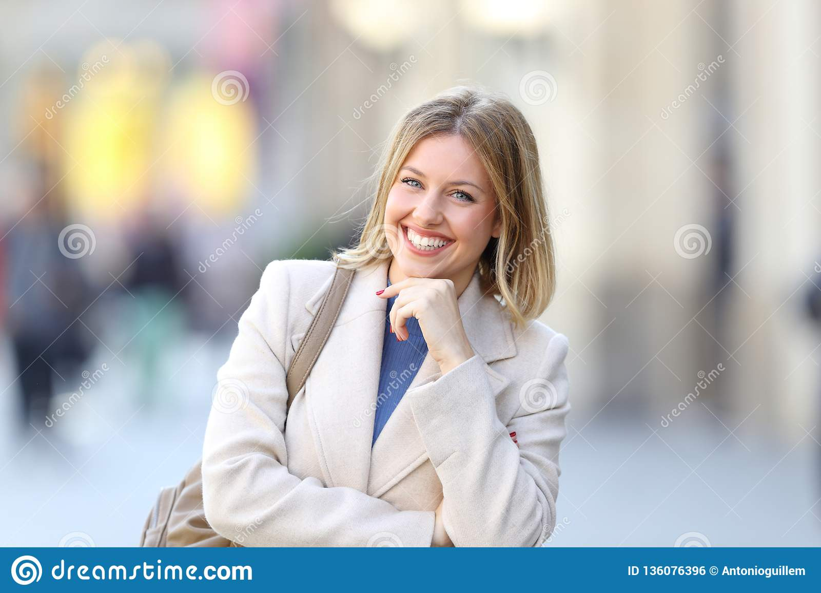 Confident woman looking at camera standing in the street