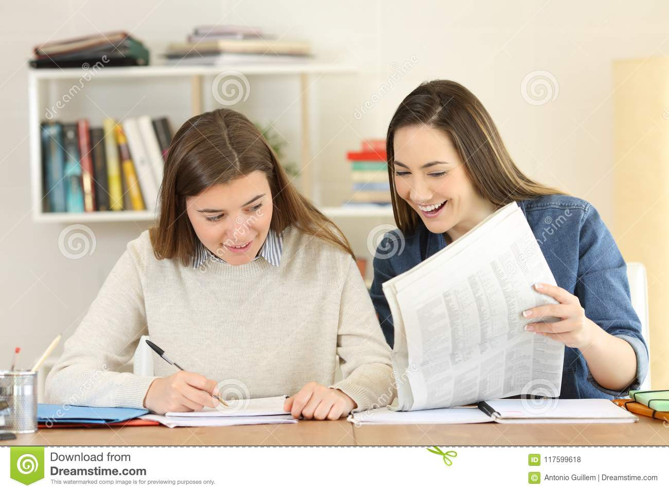 two students comparing newspaper news stock photo - image of