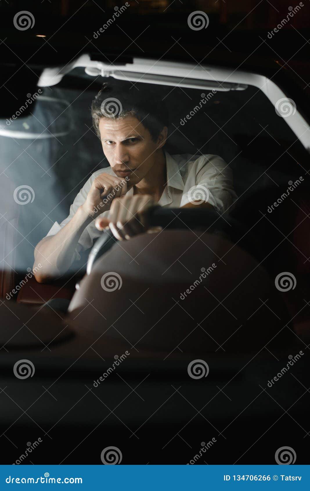 Front View Retrato de um homem considerável que conduz seu carro na noite Os sinais atrás dele