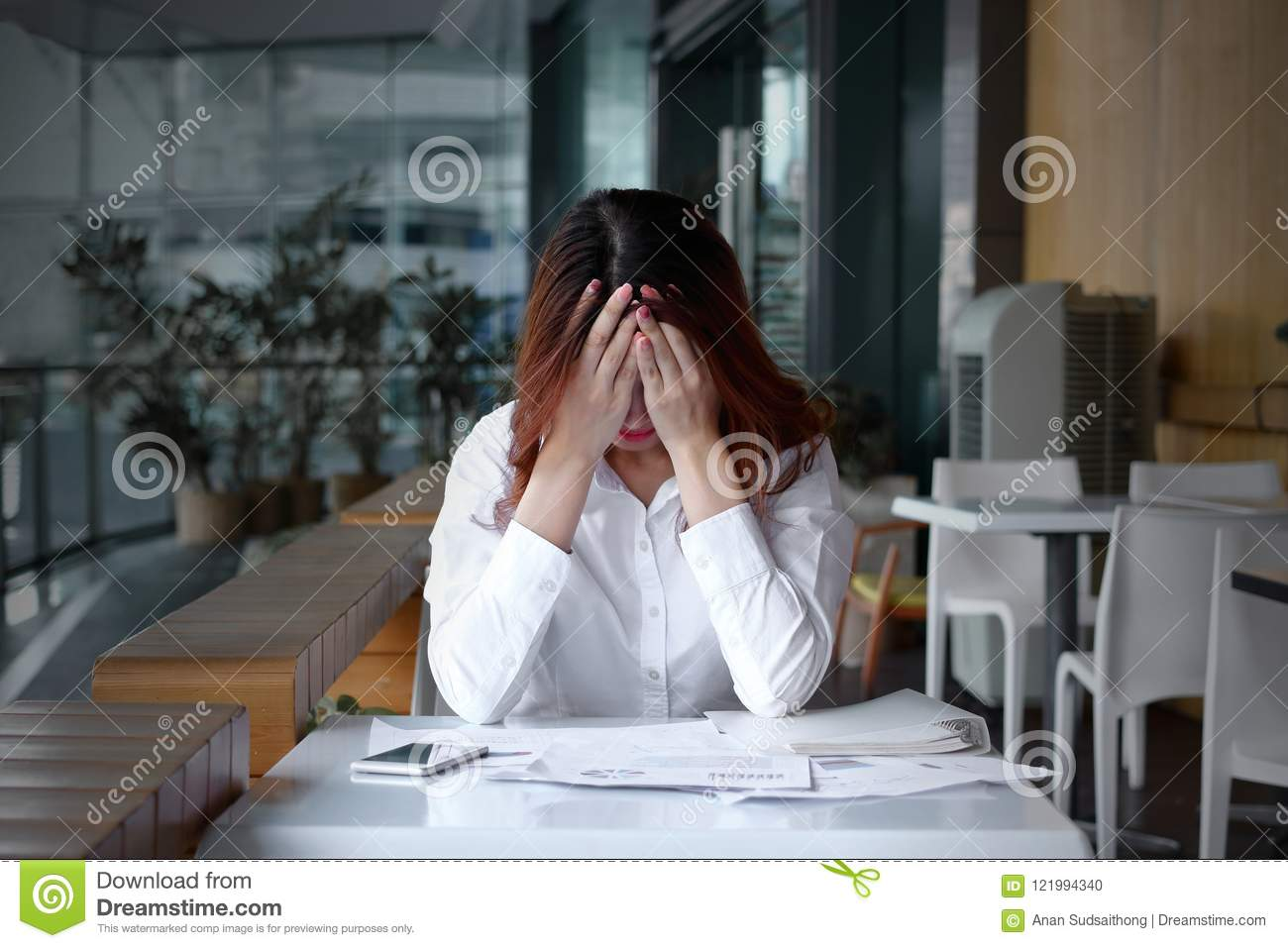 Front view of stressed frustrated young Asian business woman covering face with hands on the desk in office