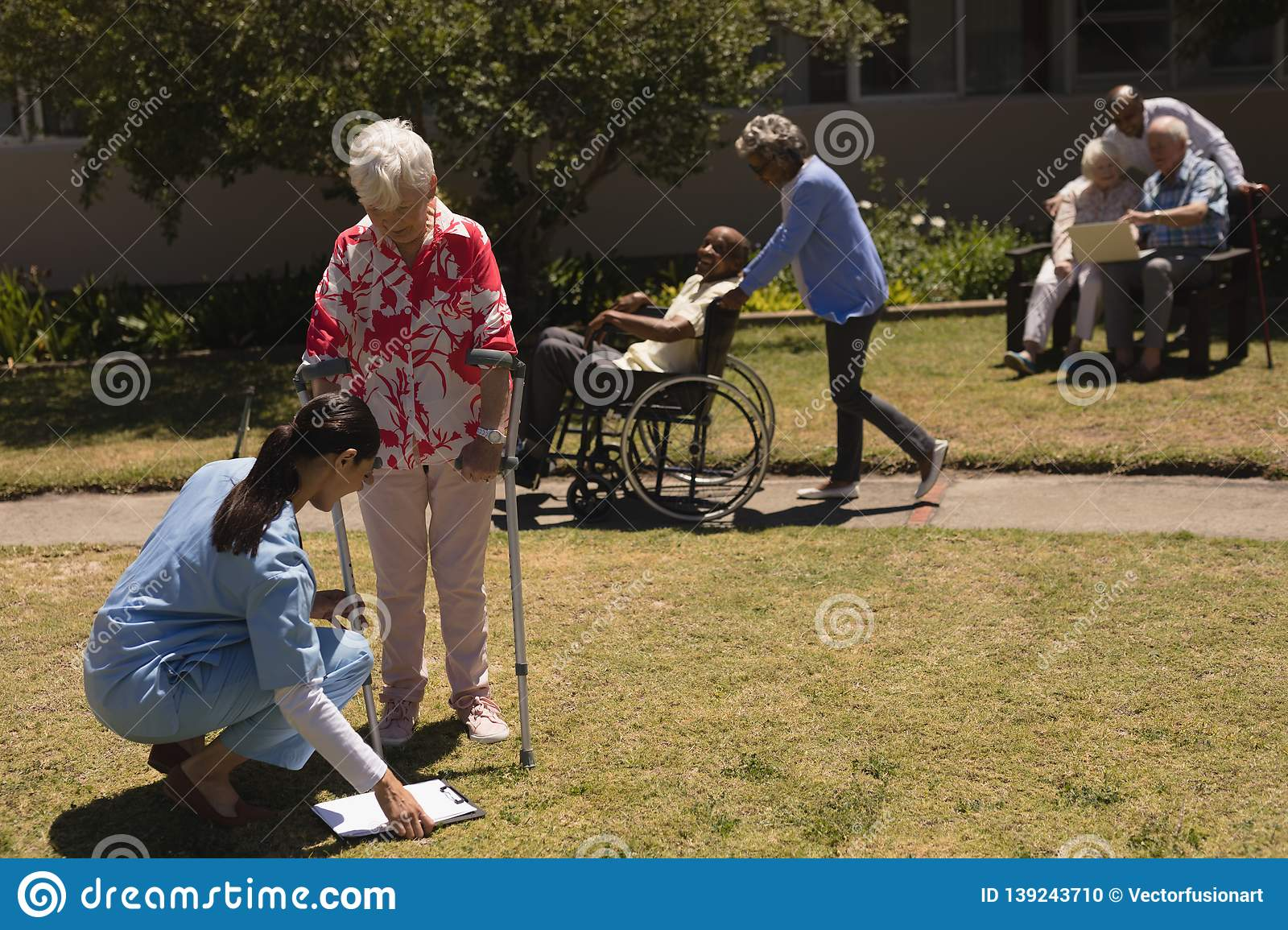 Young female doctor examining disabled senior woman in garden