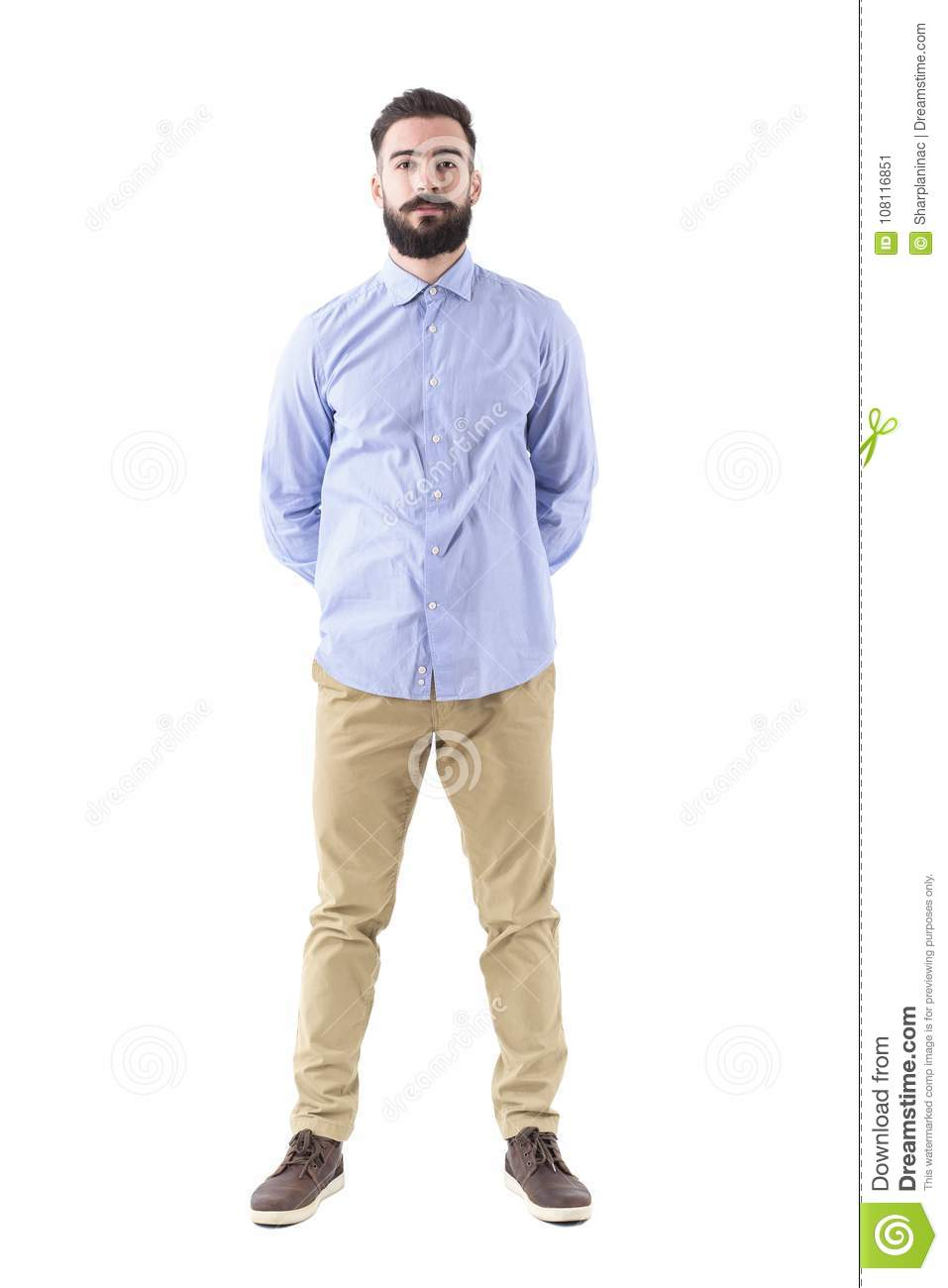 3d54eb69f4 Front view of young smart casual bearded man standing with hands on back  looking at camera. Full body length portrait isolated on white background.