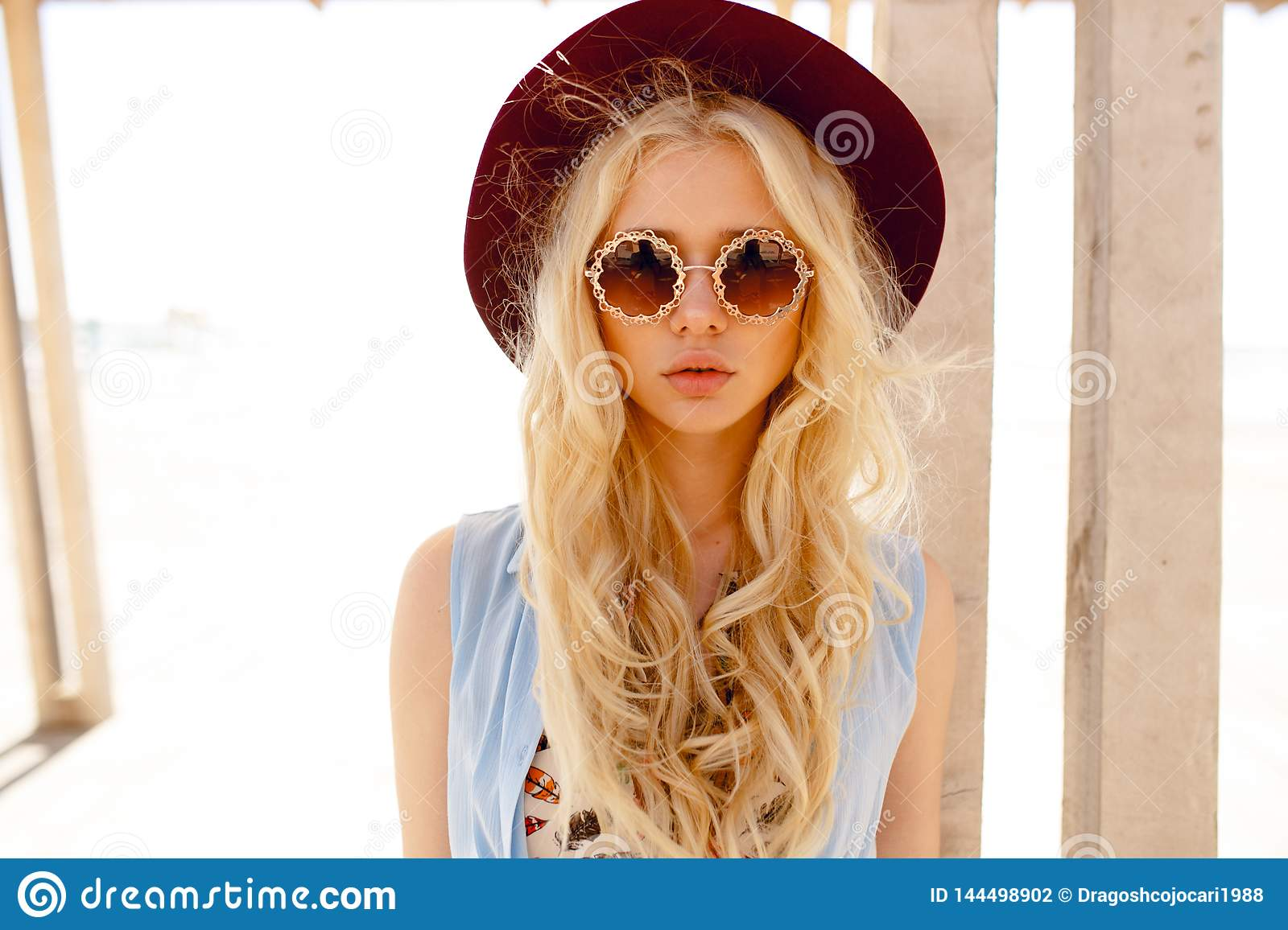 Sensual young woman with big lips, wearing in stylish hat and round sunglasses, posing outside.