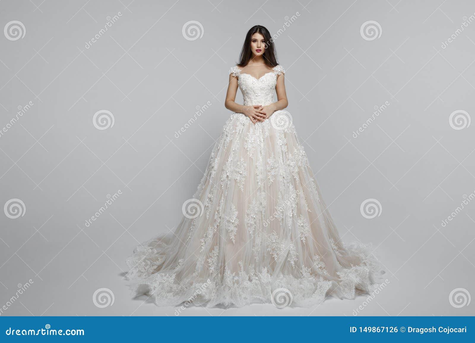 Frontal sikt av en fantastisk kvinnlig modell i wendding klänning för lång prinsessa som isoleras på en vit bakgrund