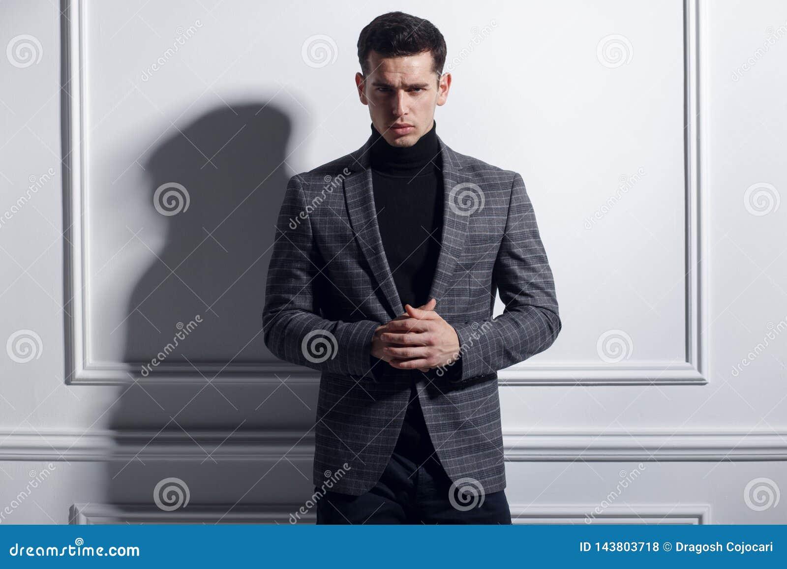 Frontal stående av stiligt elegant posera för ung man som är säkert i stilfull svart-grå färger dräkt nära den vita väggen, studi