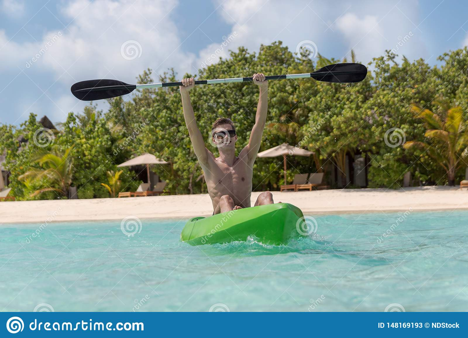 Young happy man with arms raised kayaking on a tropical island in the Maldives. Clear blue water