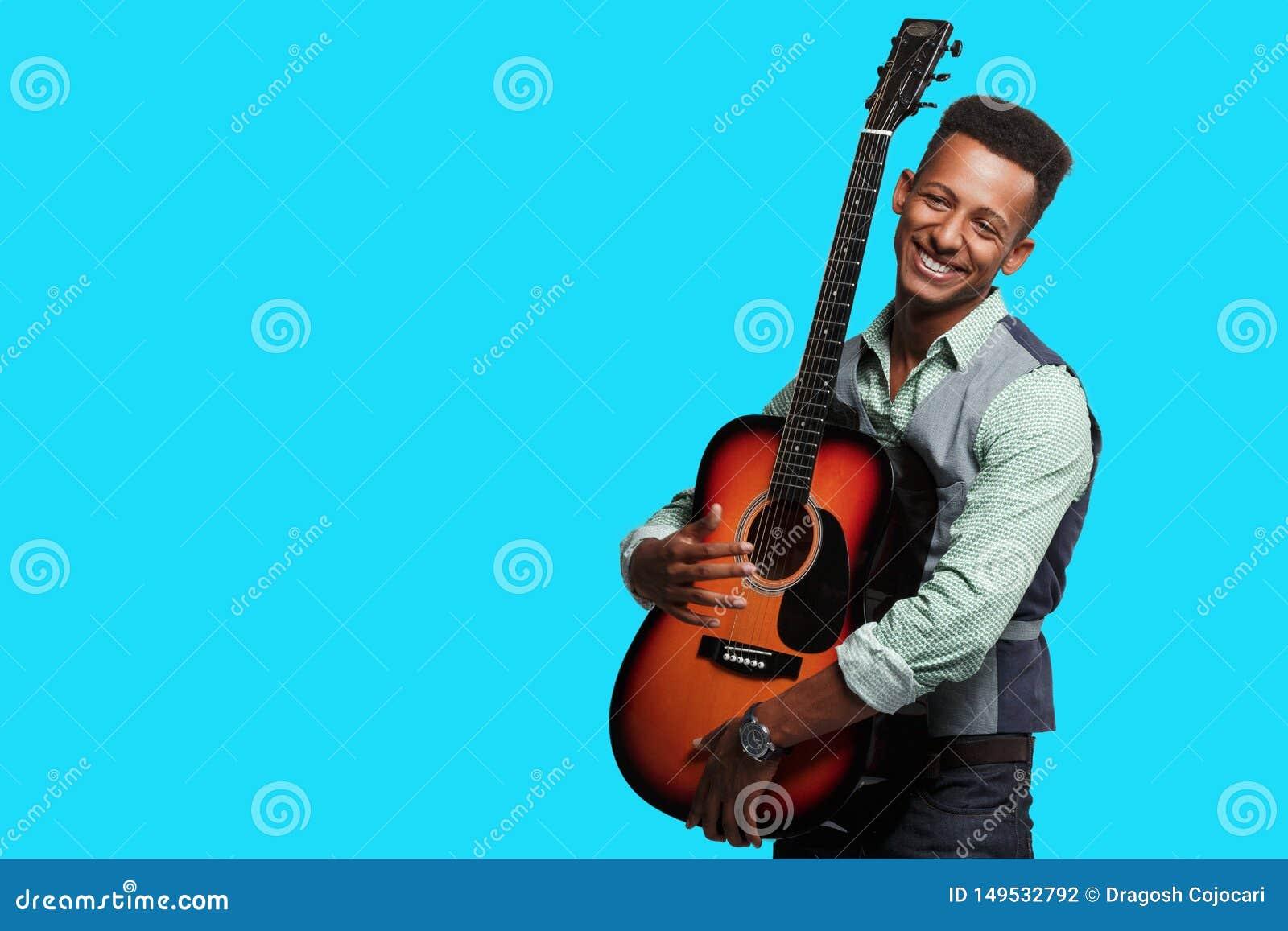 Frontale mening van een geluk gemengde ras jonge mens met gitaar in zijn wapens, speler op blauwe achtergrond, exemplaarruimte