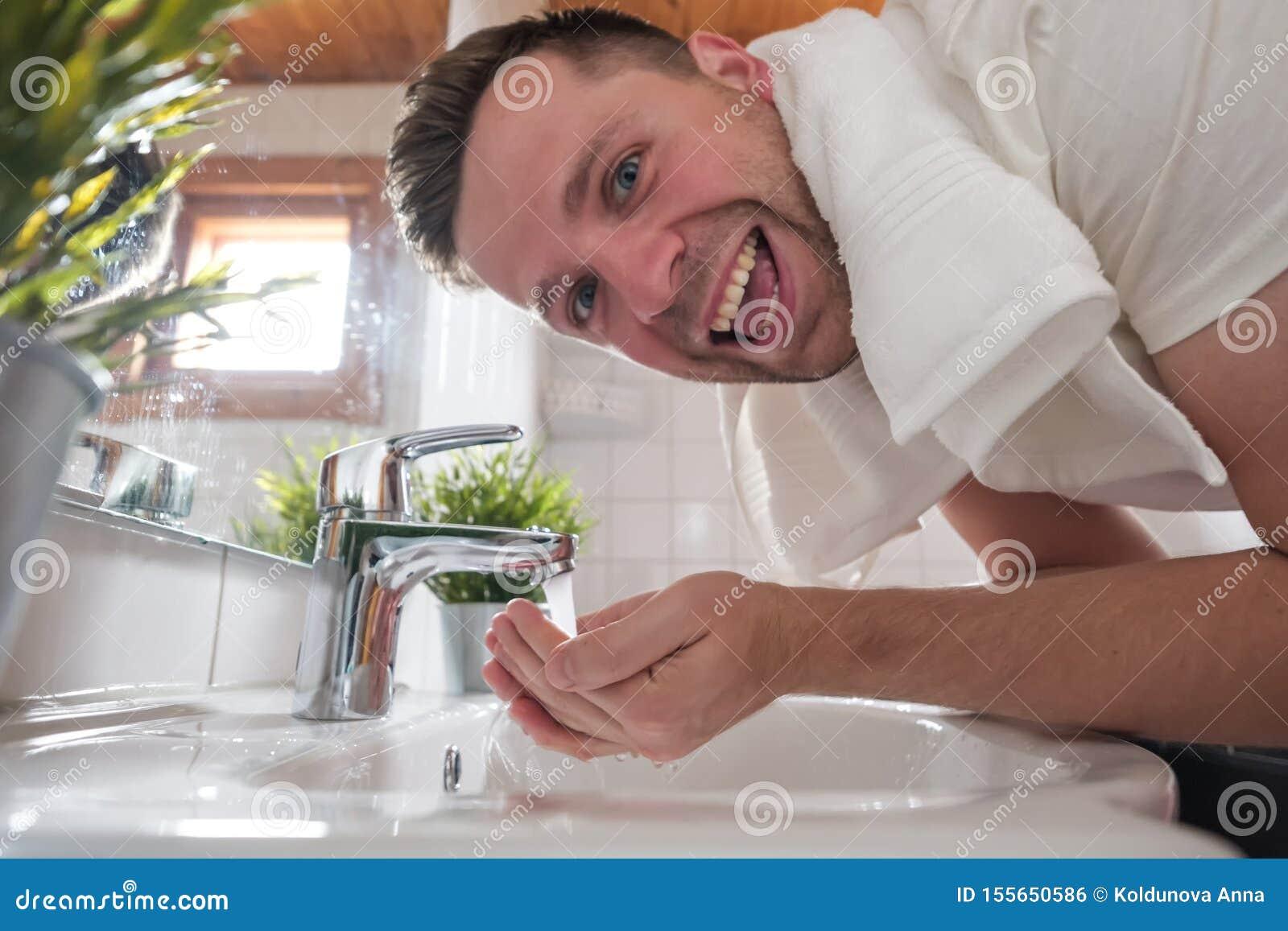 Fronte caucasico di lavaggio dell uomo in un lavabo in toilette bianca