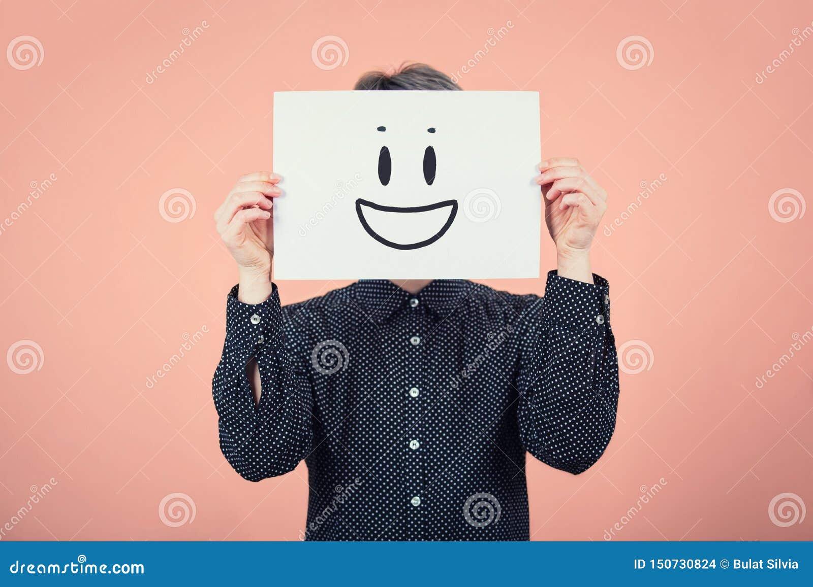 Fronte della copertura della donna di affari facendo uso di uno strato di Libro Bianco con lo schizzo dell emoticon di sorriso, c