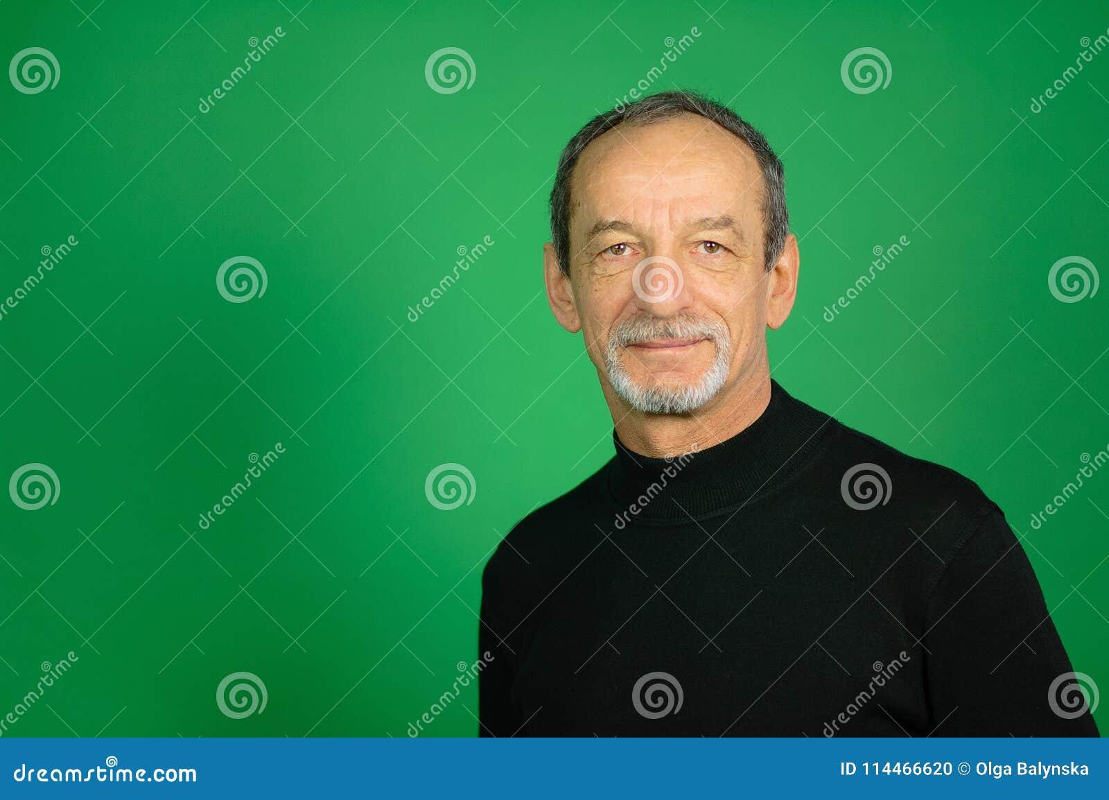 Fronte maschio dell uomo senior con la barba Ben-sistemata e di Gray Hair su un fondo verde in studio