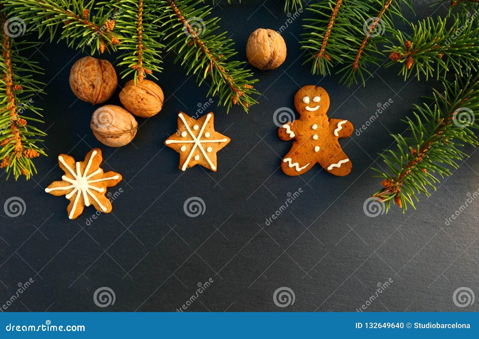 Frontera de la Navidad hecha de rama de la picea, de wallnuts y de la galleta del hombre de pan de jengibre