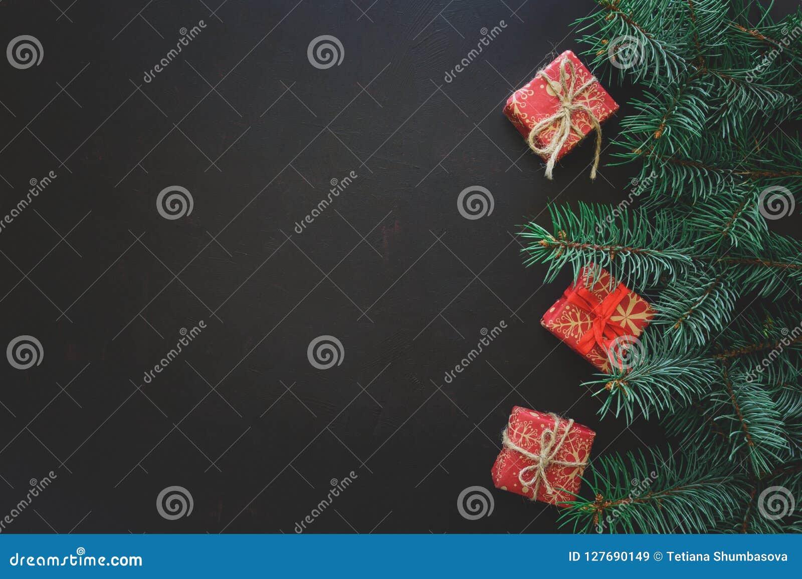 Frontera de la Navidad Ramas de árbol de abeto con las cajas de regalo en fondo de madera oscuro Visión superior Copie el espacio