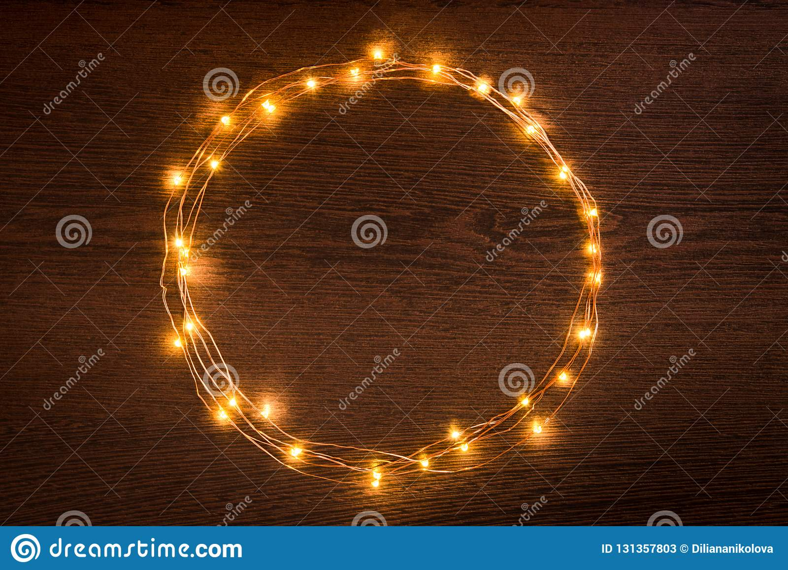 Frontière circulaire de guirlande de lumières de Noël au-dessus de fond en bois foncé Configuration plate, l espace de copie