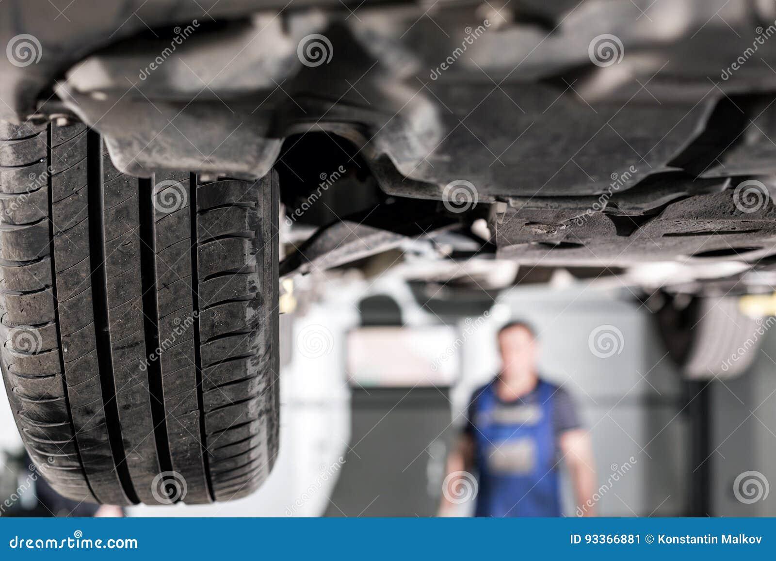 Frontowy samochodowy zawieszenie garażu mechanik podnosił samochód na dźwignięciu