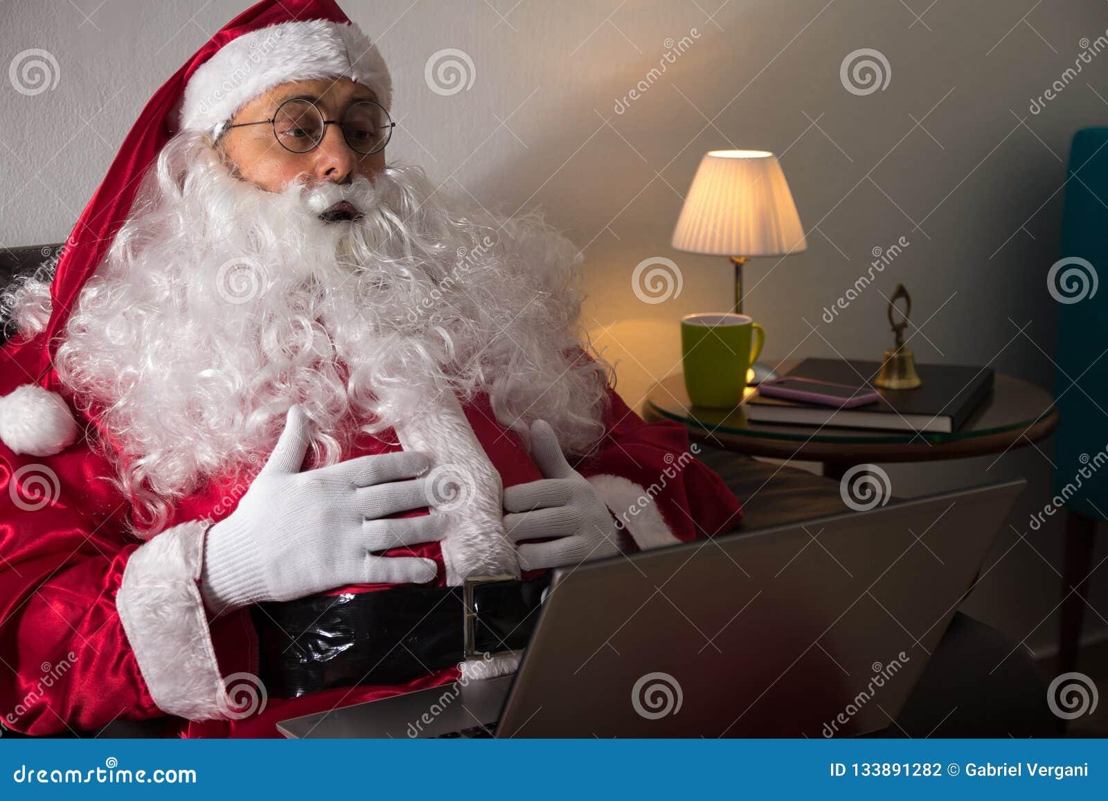Frontowy widok Święty Mikołaj obsiadanie w kanapie Używa laptop f w domu