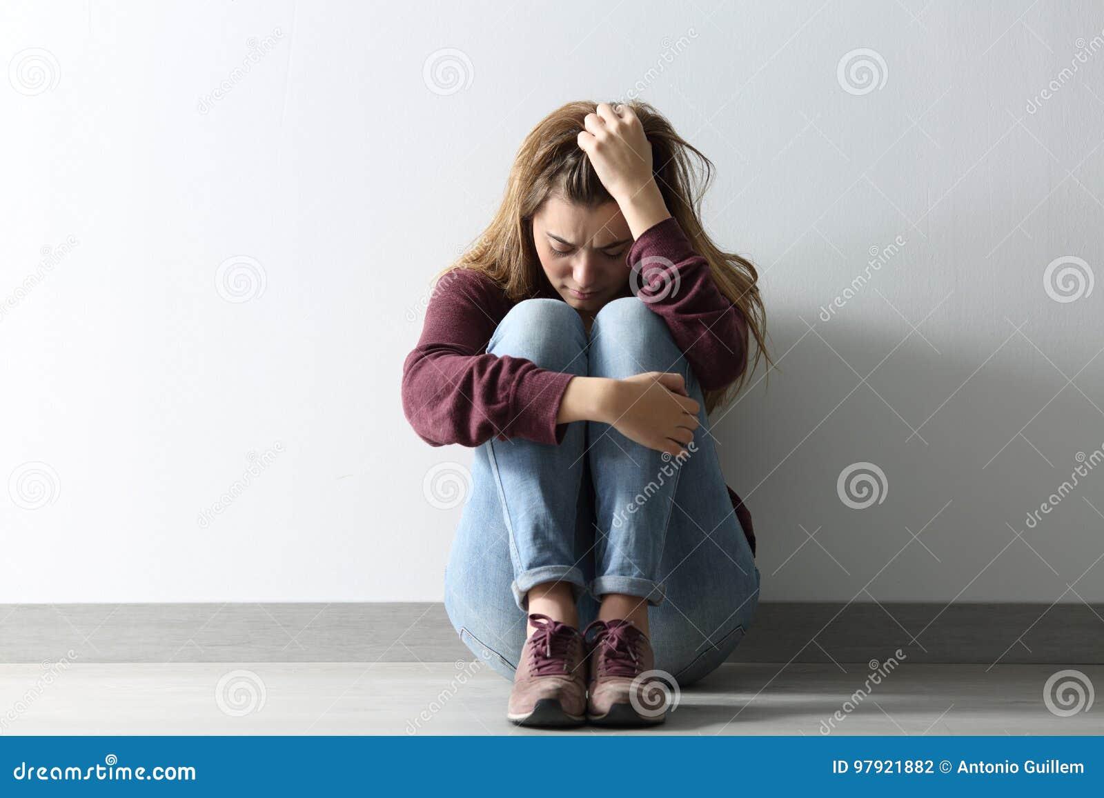 Frontowy widok smutny kobiety obsiadanie na podłoga