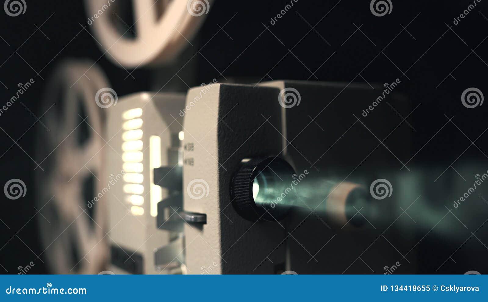 Frontowy widok staromodny antykwarski Super 8mm ekranowy projektor, projektuje promień światło w ciemnym pokoju obok a