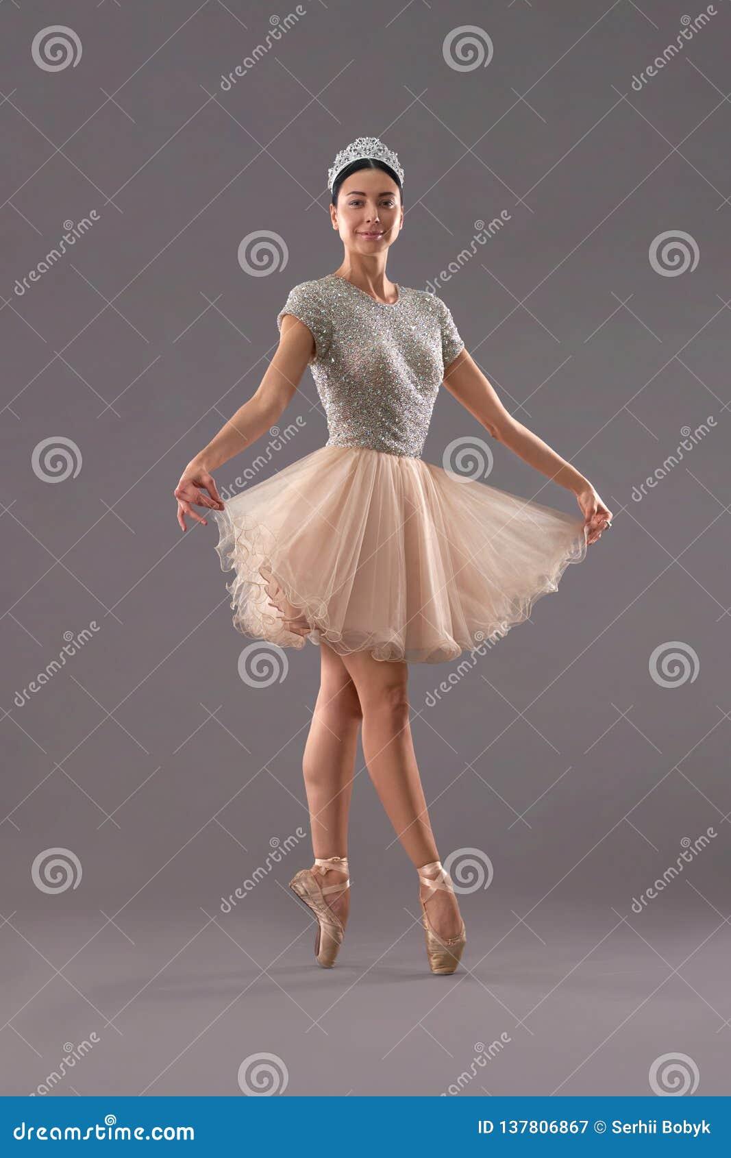 Frontowy widok utrzymuje smokingowy z palcami w studiu balerina