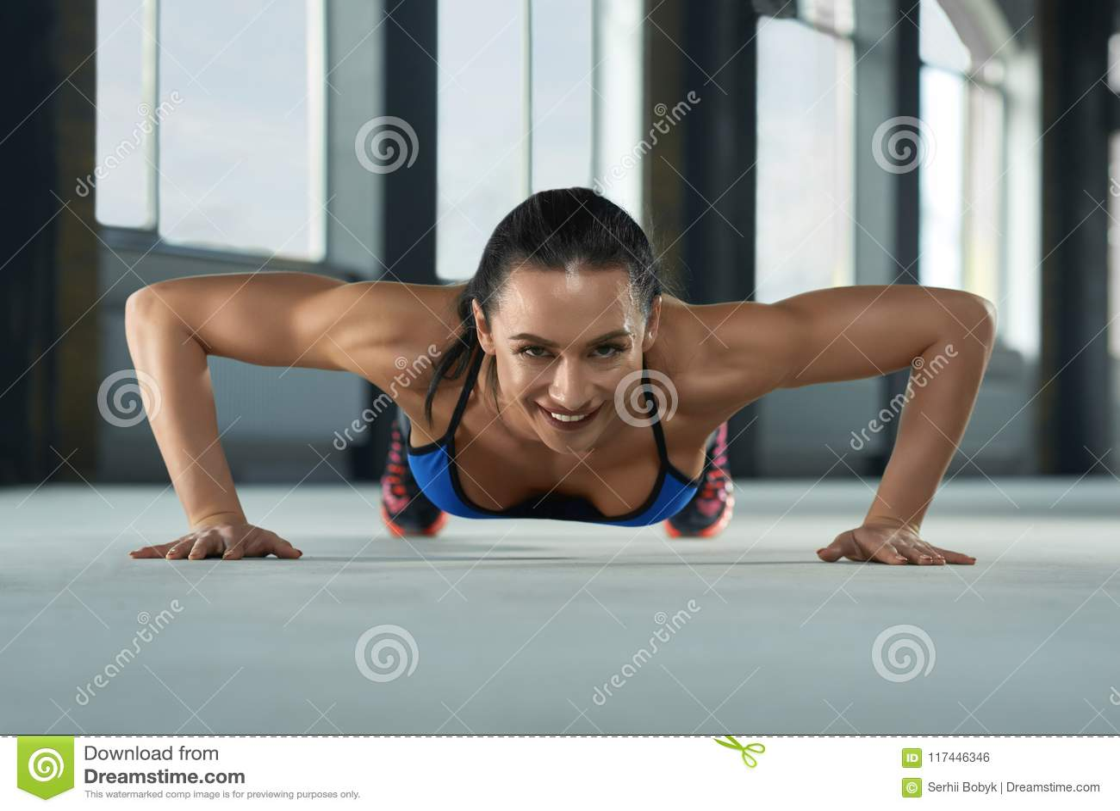 Frontview de jeune fille sportive avec le corps sportif faisant des pousées sur le plancher de gymnase