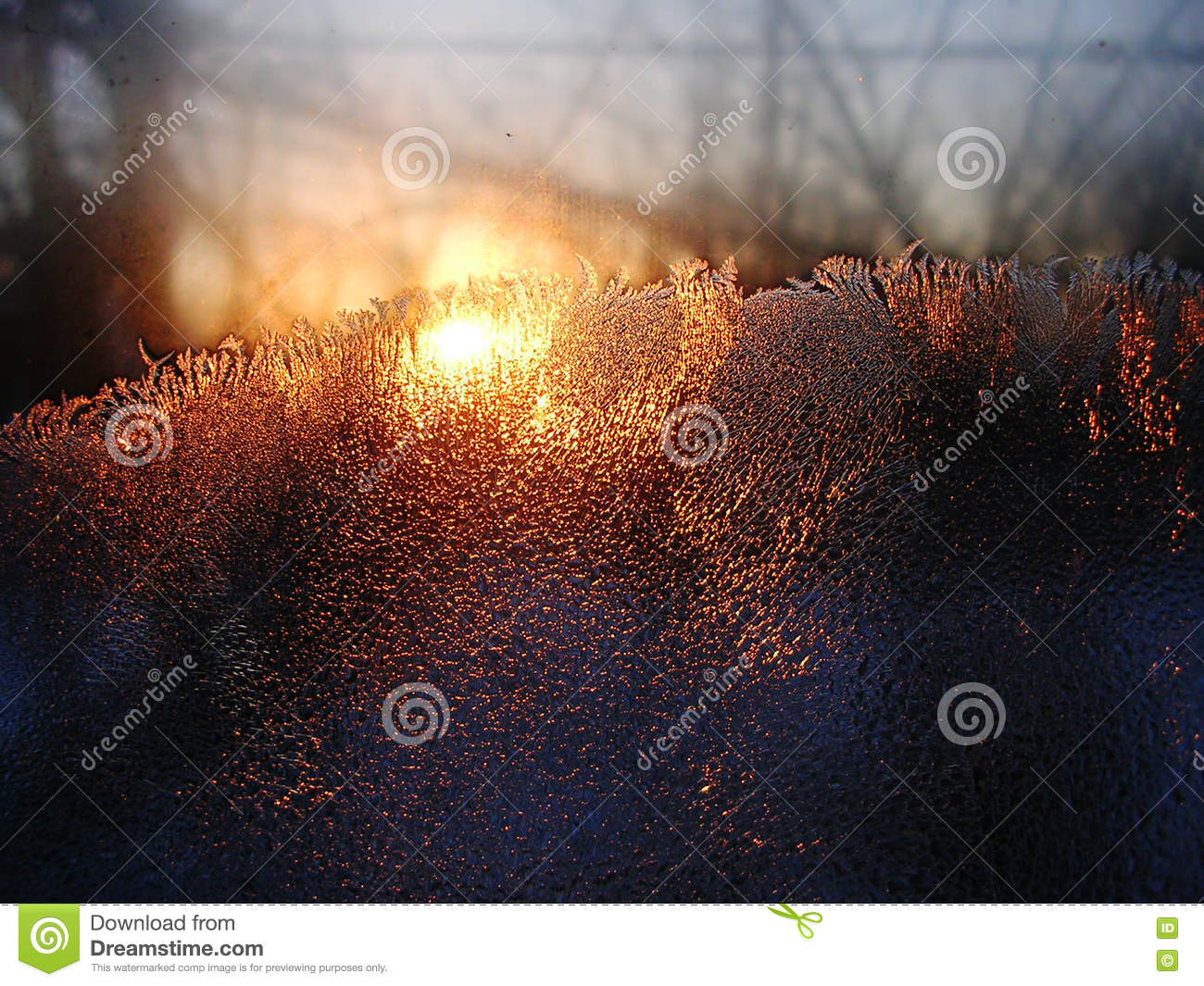Frost ice crystals and water drops on window glass on the background of sunrise.