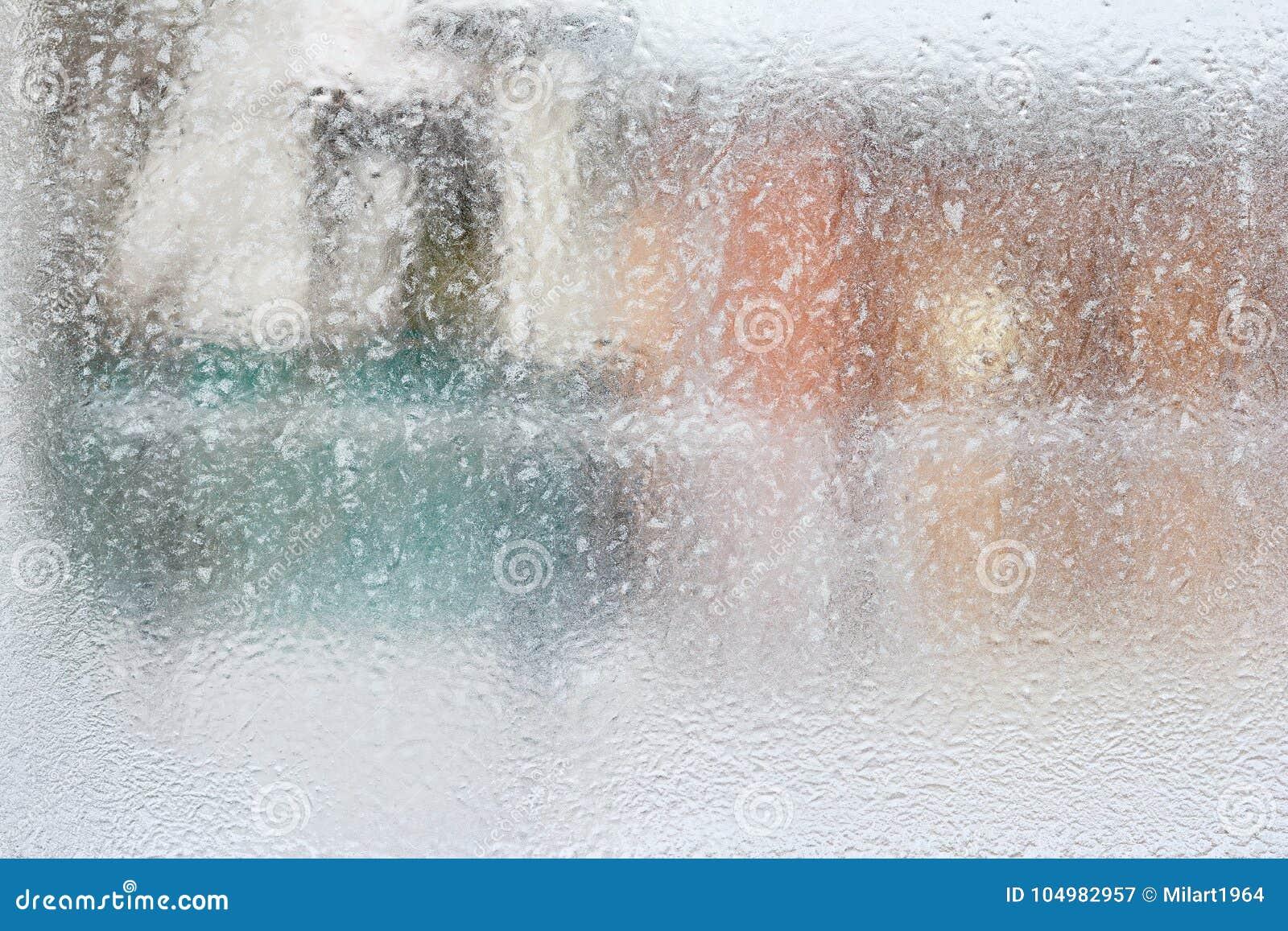 Frostig modell på det glass vinterfönstret, blick till och med exponeringsglas