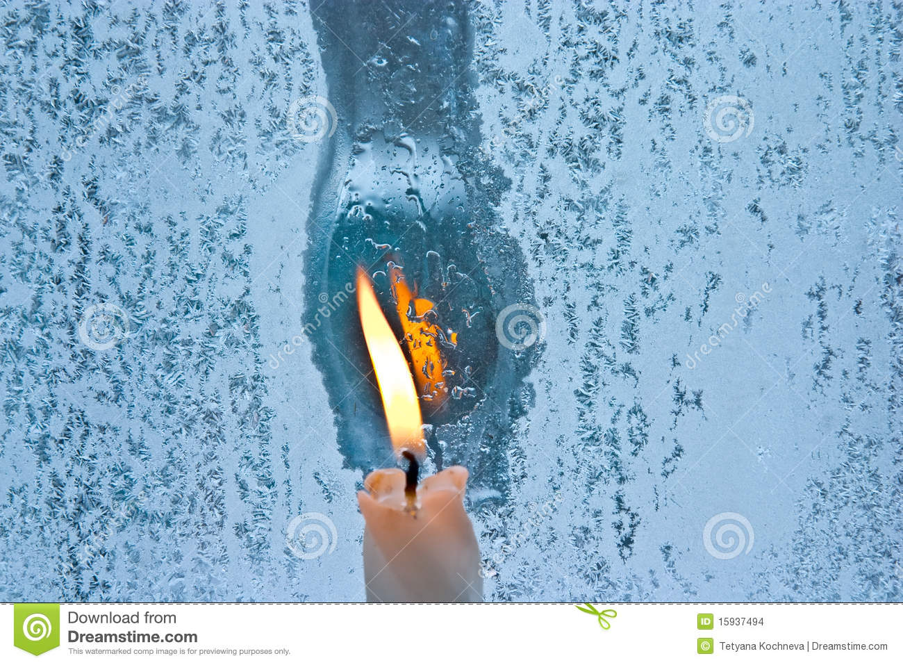 Frostwork on a window glass and candle