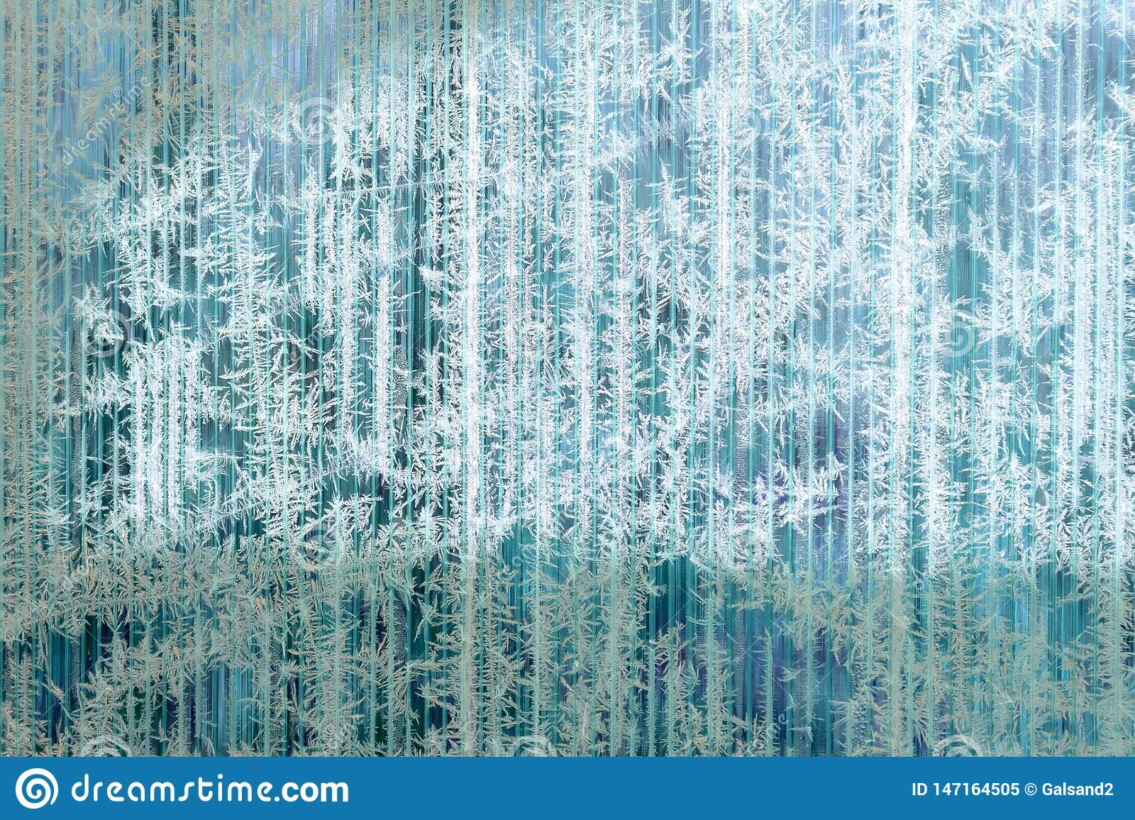Frosty pattern of hoarfrost and snowflakes on striped glass, winter or Christmas background, texture