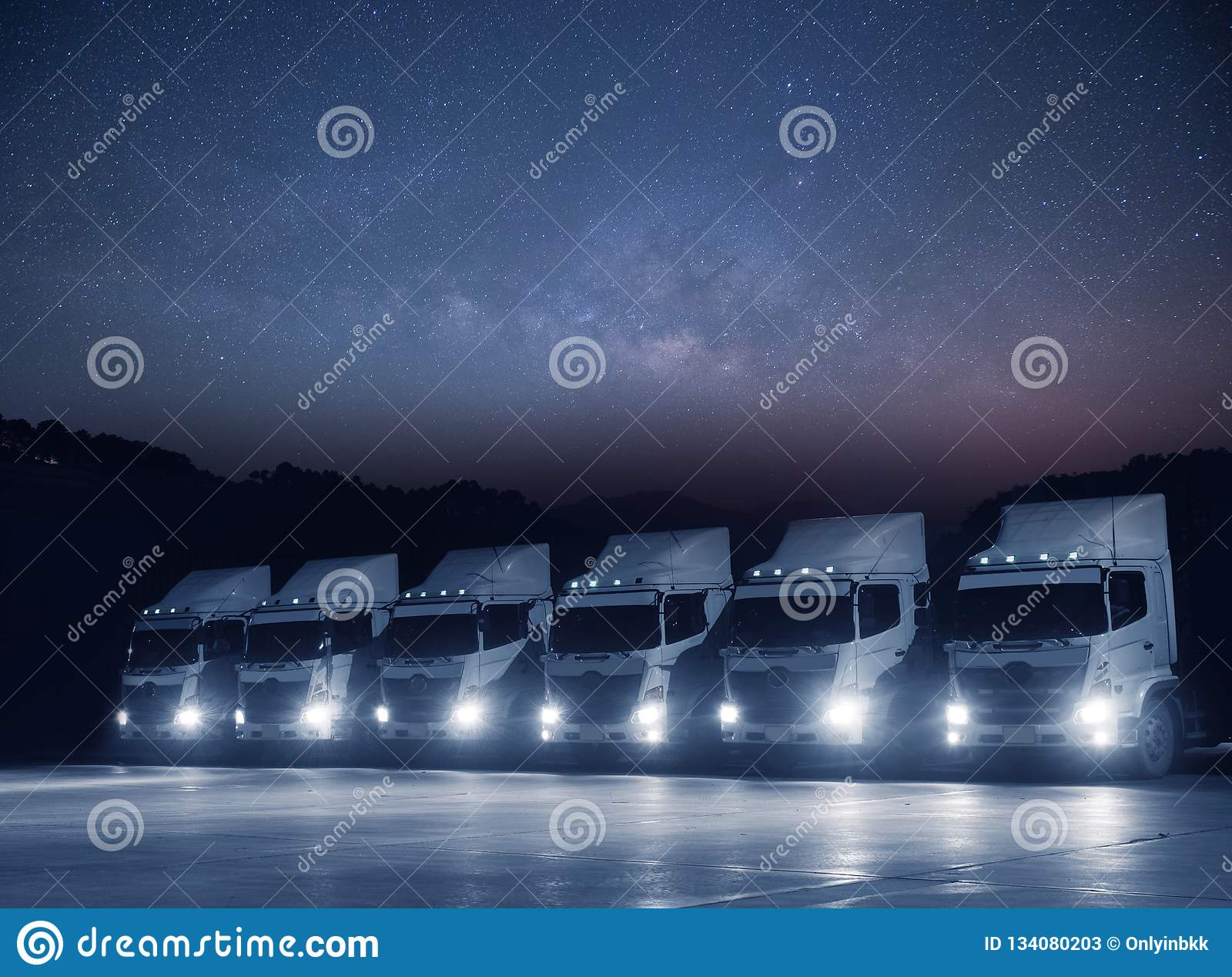 A frota branca nova do caminhão de transporte está estacionando na noite com a astronomia milkyway