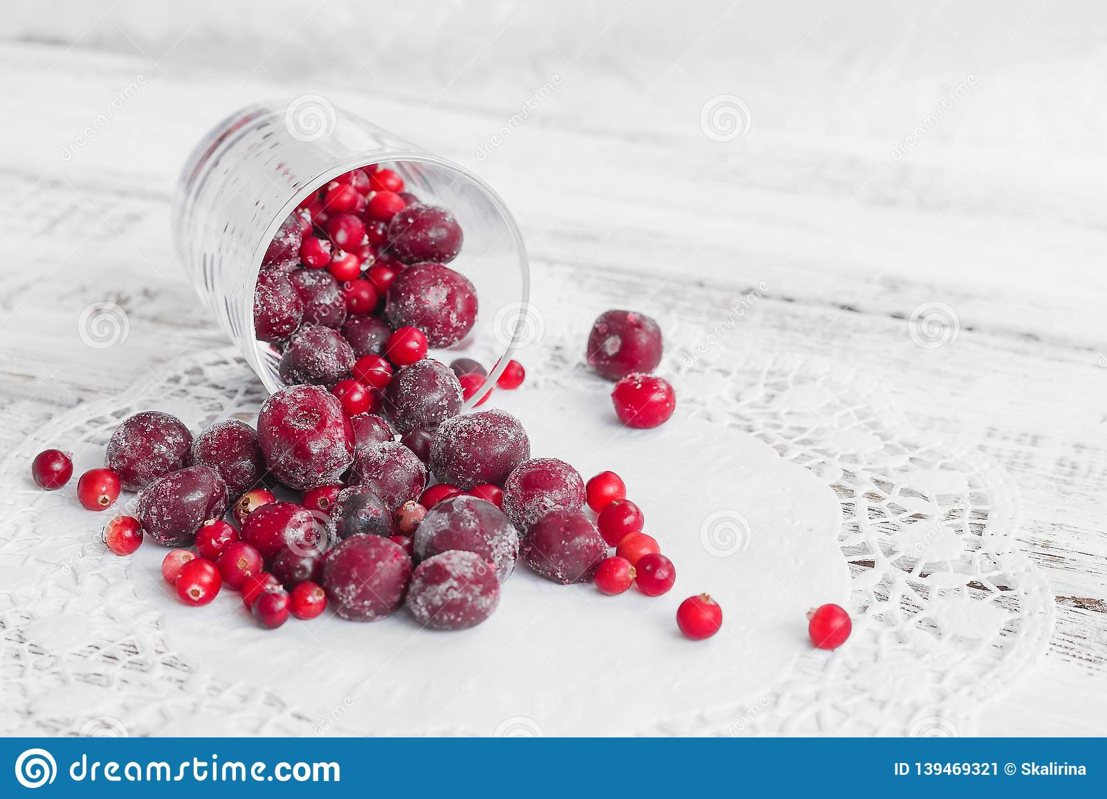 Frozen berries in a glass cup on the light wooden background. Cherry and cranberry
